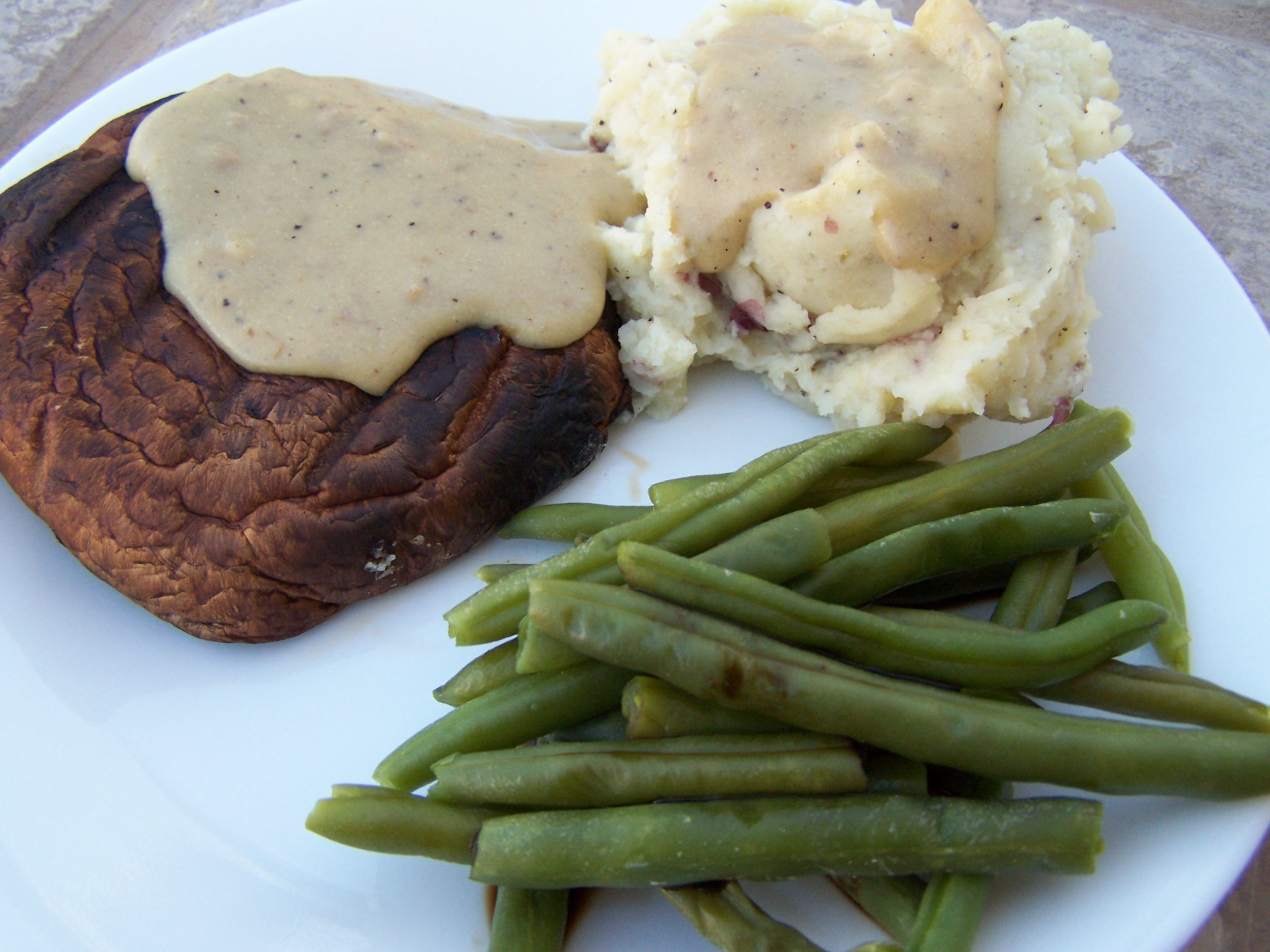 Grilled Portobello Steaks, Garlic Mashed Potatoes, green beans, and mushroom gravy.